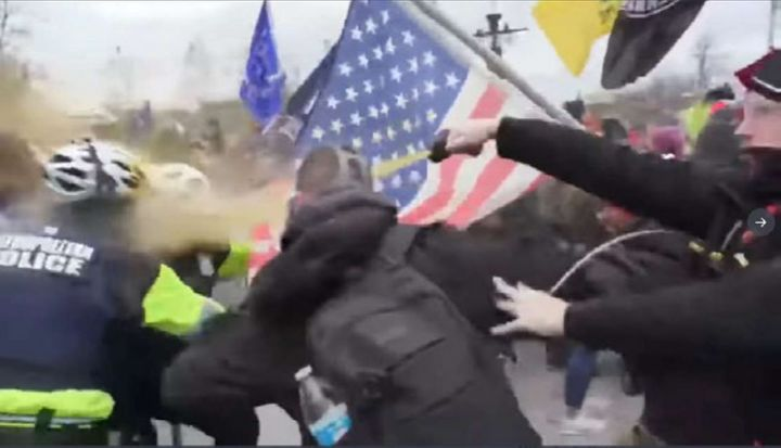 The FBI says this image shows Andrew Taake pepper spraying a D.C. Metropolitan Police officer at the Capitol on Jan. 6.