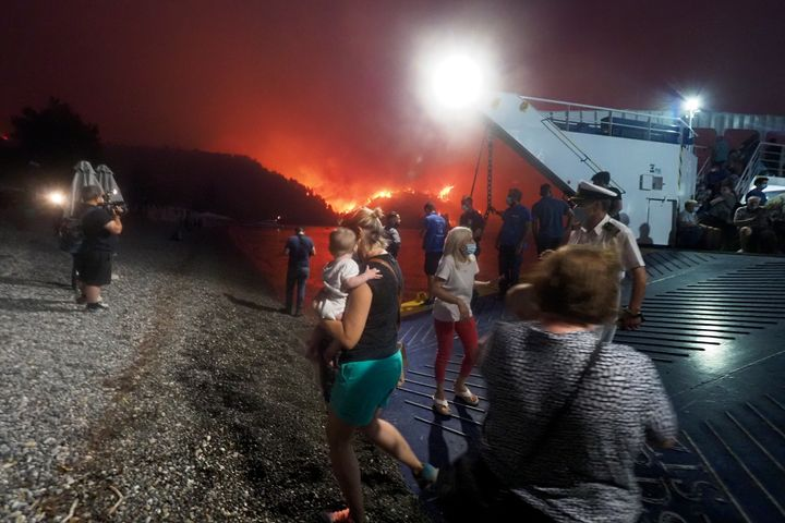 People embark a ferry during an evacuation from Kochyli beach as wildfire approaches near Limni village on the island of Evia
