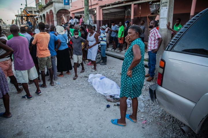 LES CAYES, HAITI - AUGUST 15:  Haitians look over a casualty in the 7.2-magnitude earthquake on August 15, 2021 in Les Cayes,