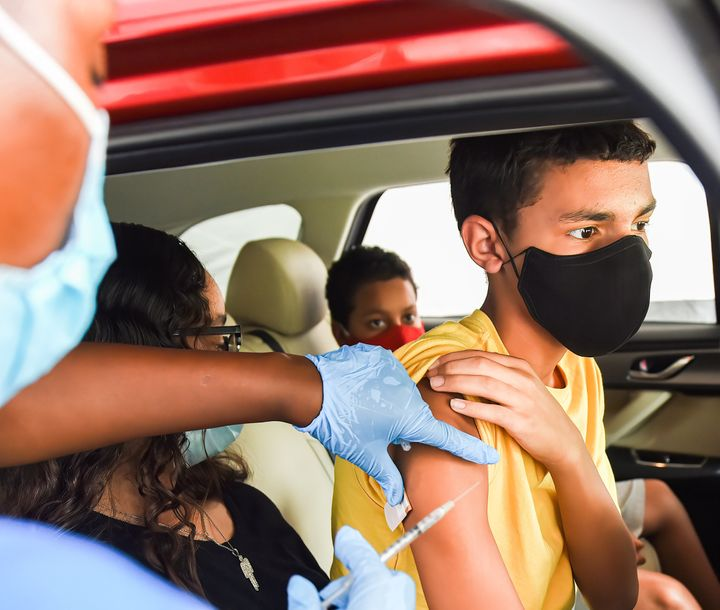 A nurse administers a COVID-19 vaccine to a kid at a drive-thru COVID-19 testing and vaccination site at Barnett Park in Orla