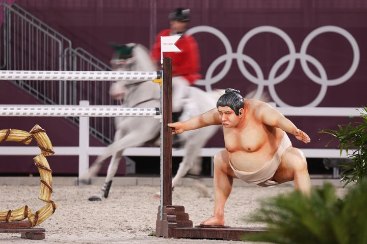 A show jumper rides behind an obstacle with a sumo wrestler beside it in an event at the Tokyo Olympics.