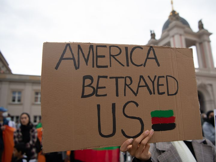 """A protester at a rally in Germany on Tuesday holds up a sign that reads, """"America Betrayed Us."""""""